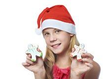 Muchacha con las galletas del hombre de pan de jengibre de la Navidad en manos Foto de archivo