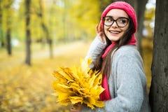 Muchacha con las hojas de arce en manos en parque del otoño Foto de archivo