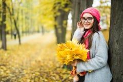 Muchacha con las hojas de arce en manos en parque del otoño Imagenes de archivo