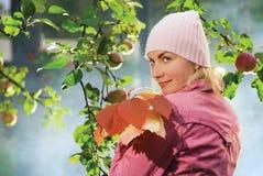 Muchacha con las hojas de otoño imagenes de archivo