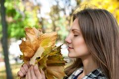 Muchacha con las hojas de otoño Foto de archivo