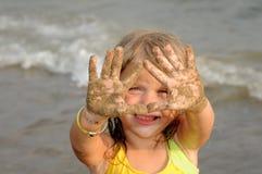 Muchacha con las manos de Sandy Imagenes de archivo