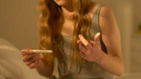 Muchacha con las manos de temblor que llevan a cabo la prueba de embarazo, para resultado negativo que espera metrajes