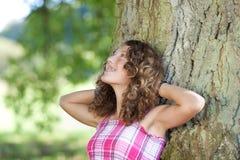 Muchacha con las manos detrás de la cabeza que se inclina en tronco de árbol Foto de archivo