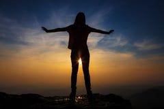 Muchacha con las manos extendidas en la silueta de la puesta del sol Fotos de archivo libres de regalías
