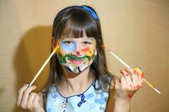 Muchacha con las manos pintadas Retrato de un niño manchado con las pinturas Imagenes de archivo