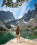 Muchacha con las manos que se levantan en la roca en caminar viaje en montañas Imagenes de archivo