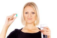 Muchacha con las píldoras y vidrio de agua imagen de archivo