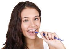 Muchacha con las paréntesis que aplican sus dientes con brocha Foto de archivo libre de regalías