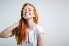 Muchacha con las pecas que sonríe con los ojos cerrados que tocan su pelo rojo Imagen de archivo libre de regalías