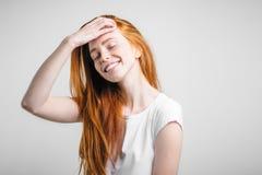 Muchacha con las pecas que sonríe con los ojos cerrados que tocan su pelo rojo Fotografía de archivo