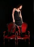 Muchacha con las perlas en sillas foto de archivo