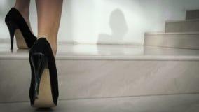 Muchacha con las piernas hermosas que suben las escaleras almacen de metraje de vídeo