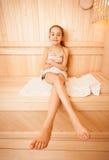 Muchacha con las piernas largas que se sientan en la toalla en la sauna Foto de archivo