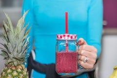 Muchacha con las tazas del tarro de albañil a disposición llenadas del smoothie rojo de las frutas foto de archivo