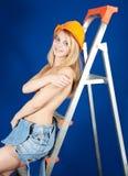 Muchacha con las tetas al aire en sombrero duro en el stepladder Imagen de archivo libre de regalías