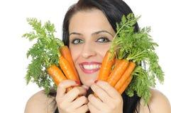 Muchacha con las zanahorias frescas Foto de archivo libre de regalías