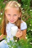 Muchacha que sostiene el vidrio de leche en manos Foto de archivo