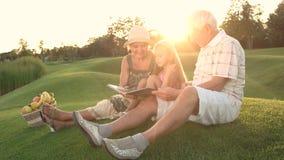 Muchacha con los abuelos al aire libre, álbum de foto almacen de metraje de vídeo
