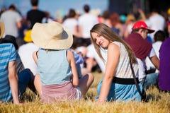 Muchacha con los amigos, adolescentes, festival del verano, sentándose en hierba Foto de archivo libre de regalías