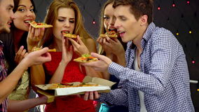 Muchacha con los amigos que bailan y que comen la rebanada de pizza en club nocturno 4K metrajes