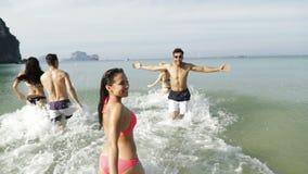 Muchacha con los amigos que corren en agua que llama le para unirse a, a la gente que salpica el hombre joven y al grupo de la mu almacen de metraje de vídeo