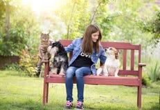 Muchacha con los animales domésticos en parque Imagen de archivo libre de regalías