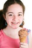 Muchacha con los apoyos que come el helado Fotos de archivo