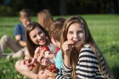 Muchacha con los apoyos que come las uvas Fotografía de archivo
