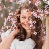 Muchacha con los apoyos que llevan a cabo la rama de árbol floreciente Foto de archivo libre de regalías