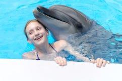 Muchacha con los apoyos que sonríe y que juega con el delfín en piscina Fotos de archivo libres de regalías