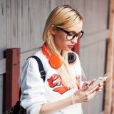 Muchacha con los auriculares anaranjados que buscan la pista impresionante en su teléfono Fotos de archivo