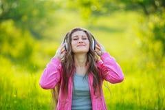 Muchacha con los auriculares blancos Foto de archivo