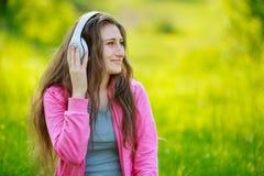 Muchacha con los auriculares blancos Fotografía de archivo