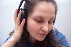 Muchacha con los auriculares con los ojos cerrados Imagen de archivo libre de regalías