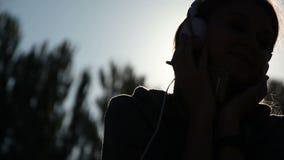 Muchacha con los auriculares delante de la luz del sol brillante almacen de metraje de vídeo