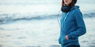 Muchacha con los auriculares en el fondo del mar Foto de archivo libre de regalías