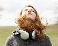 Muchacha con los auriculares en el resorte al aire libre. Imagenes de archivo