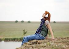 Muchacha con los auriculares en la roca Imagen de archivo libre de regalías