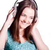 Muchacha con los auriculares que canta en el fondo blanco Imágenes de archivo libres de regalías