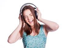 Muchacha con los auriculares que canta en el fondo blanco Fotos de archivo