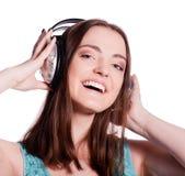 Muchacha con los auriculares que canta en el fondo blanco Imagenes de archivo