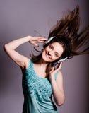 Muchacha con los auriculares que canta en el fondo blanco Imagen de archivo