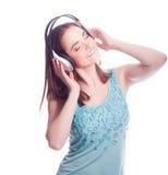 Muchacha con los auriculares que canta en el fondo blanco Fotografía de archivo