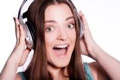 Muchacha con los auriculares que canta en el fondo blanco Foto de archivo libre de regalías