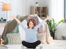 Muchacha con los auriculares que escucha la música en casa Fotos de archivo libres de regalías