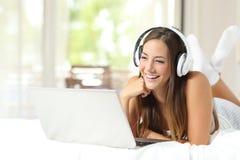 Muchacha con los auriculares que lee en un ordenador portátil en casa Fotografía de archivo libre de regalías