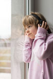 Muchacha con los auriculares que miran a través de ventana Imagen de archivo libre de regalías