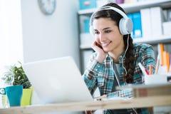 Muchacha con los auriculares usando un ordenador portátil Fotos de archivo