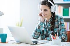 Muchacha con los auriculares usando un ordenador portátil Fotos de archivo libres de regalías
